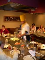 Energetic Chef at the hibachi grill moving fast
