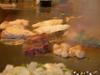 Large portions of food sizzle and steam on the hibachi grill