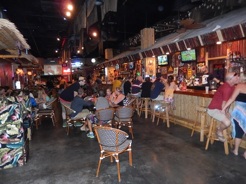 Inside seating for the 8th Ave Tiki Bar and Grill has a long bar and entertainment area.